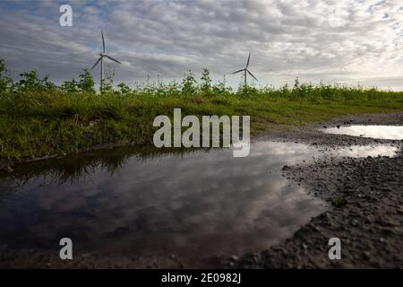 wind farm che fornisce energia pulita con il cielo nuvoloso bello che riflette in una pozza in primo piano Foto Stock
