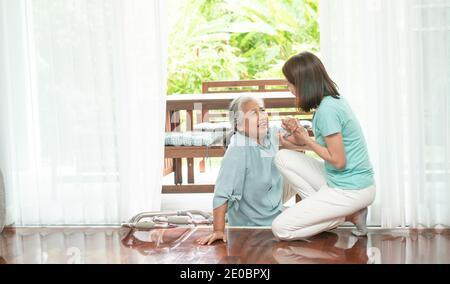 Donna anziana asiatica che cadde sul pavimento sdraiato a casa dopo che si è inciampata alla soglia e gridando nel dolore e l'infermiera è venuto per aiutare il sostegno. Concetto o