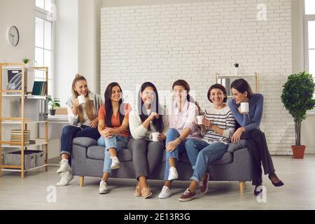 Gruppo di donne felici che parlano, divertendosi e gustando insieme una tazza di buon caffè