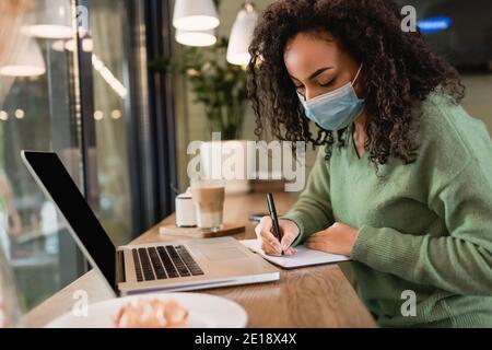 donna afroamericana in maschera medica di scrittura in notebook vicino computer portatile con schermo vuoto sul tavolo
