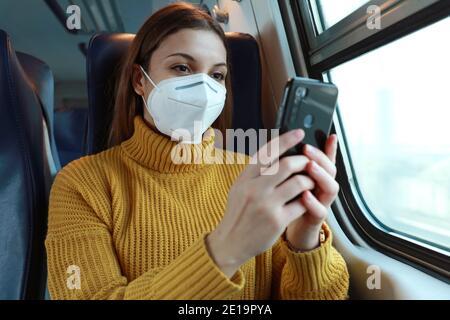 Donna rilassata con maschera facciale FFP2 KN95 con l'app per smartphone. Treno passeggeri con maschera protettiva che viaggia in business class testando su mobi