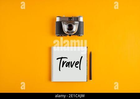 Fotocamera d'epoca con un notebook con la parola viaggio su sfondo giallo. Concetto di fotografia di viaggio.