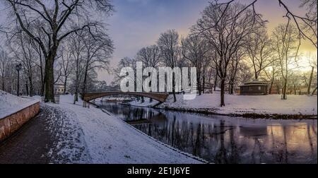 Paesaggio invernale panoramico con alba in un parco innevato con bellissimo ponte su un piccolo canale, luce di strada e coperto di tretelle da neve. Vista della Bastione Foto Stock
