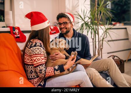 Coppia che passa la vigilia di Natale a casa. Ragazza che tiene il cane e l'uomo che legge un libro. A testa cappello di babbo natale. Concetto di vacanze di Natale.