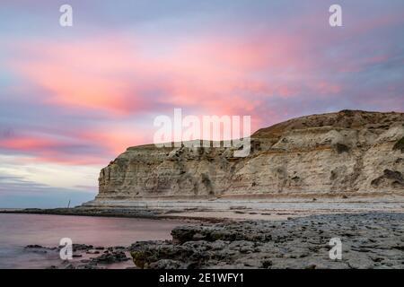 Un tramonto rosa sulle scogliere calcaree di Port Willunga spiaggia in Australia del Sud il 1 gennaio 2021 Foto Stock