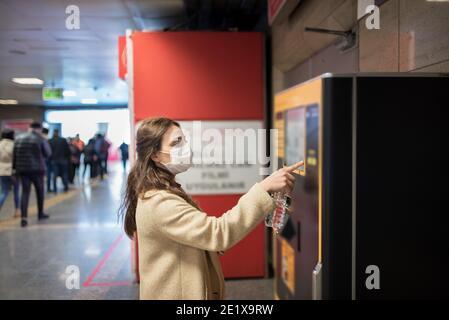 Bella ragazza che indossa maschera medica protettiva e abiti alla moda utilizza ATM macchina per money.New concetto normale durante pandemia corona, covid19.
