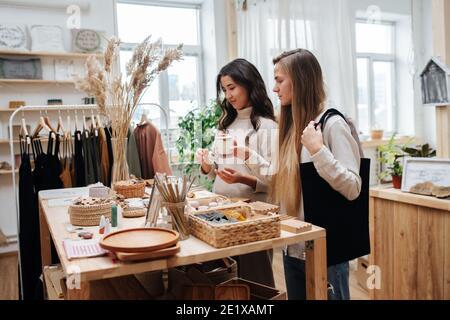 Le giovani donne vicine in piedi nel negozio ecologico scelgono tra cosmetici prodotti