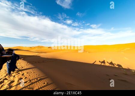 (Fuoco selettivo) vista mozzafiato della silhouette di due persone che cavalcano cammelli sulle dune di sabbia a Merzouga, Marocco.