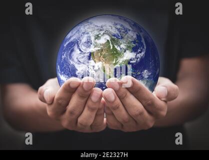 Giorno della terra. Mani umane che tengono globale su sfondo nero sfocato. Terra nelle mani. Salvare la terra. Ambiente concetto.