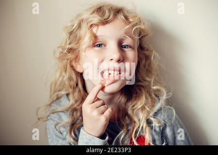 Cute caucasica bionda ragazza mostrando il suo dente mancante in bocca. Bambino orgoglioso che mostra il dente perso e si aspetta una fata dente che dà i suoi soldi. Ringhino Foto Stock