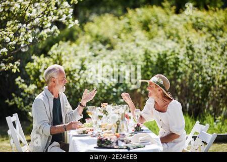 Coppia che mangiano in giardino