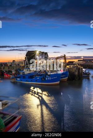 Navi da pesca nel porto di Whitstable illuminate al tramonto sulla costa del Kent settentrionale.