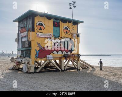 bella e divertente capanna bagnino con muro dipinto e un uomo in piedi sulla spiaggia di sabbia accanto ad esso.