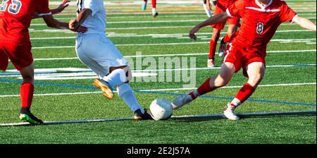 Due giocatori di calcio maschile della scuola superiore che si combattono l'un l'altro per la palla durante una partita su un campo di erba verde. Foto Stock