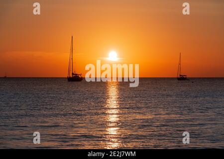 Due barche a vela che attraversano l'oceano contro un tramonto dorato. Concetto di viaggio Foto Stock