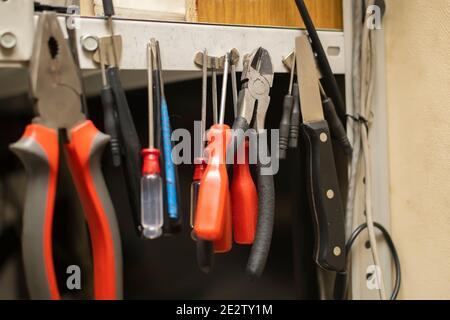 un set di attrezzi diversi vecchi e usurati si aggancia magneti su un rack metallico nel centro di assistenza