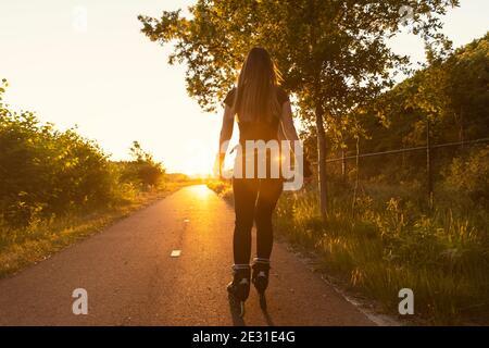 Una giovane donna roller blading su una strada con verde sullo sfondo durante il tramonto. Essere sportivo, sano stile di vita. L'ora d'oro e il sole si riacutizzano