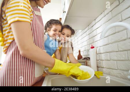 Due ragazze imparano a fare le faccende domestiche e a guardare la madre lavare i piatti dopo pranzo Foto Stock
