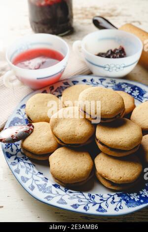 Biscotti fatti in casa con marmellata o confettura di prugne di frutta in un piatto - primo piano vista frontale cotta cibi dolci tradizionali ricetta - concetto di alimentazione sana Foto Stock