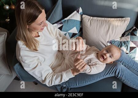 Giovane madre caucasica che si diverte sul divano con il bambino a casa durante la quarantena del coronavirus covid-19. Allontanamento sociale e isolamento di sé. Madre