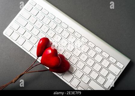 Foto della tastiera bianca e della forma del cuore rosso. Foto Stock