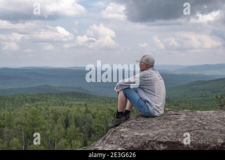 Un uomo libero, di mezza età, siede sulla cima della montagna e gode di una splendida vista sulla valle di montagna. Concetto di viaggio. Solitudine, unità con la natura.