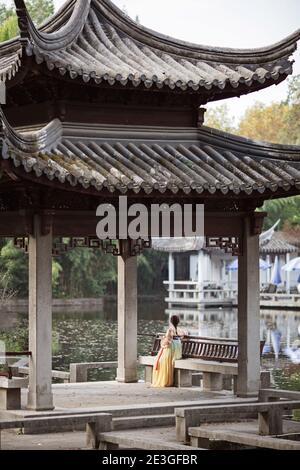 Huzhou, Cina, 18 novembre 2020: Donna cinese che indossa abiti tradizionali e tiene fan nel parco in Cina. Happy Spring Festival, Capodanno cinese Foto Stock