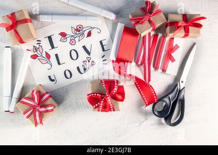 Nastri rossi, regali, forbici, pennarelli accanto a San Valentino con parole Ti voglio bene. Preparazione per San Valentino. Concetto di San Valentino. Disposizione piatta. Vista dall'alto