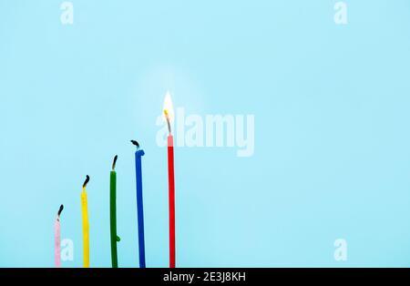 Gruppo di candele bruciate e una rossa alta che brucia su sfondo azzurro. Idea, concetto di successo. Molto spazio per la copia. Foto Stock