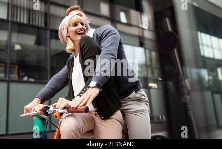 Ritratto di felice giovane coppia a cavallo di una bicicletta e divertirsi insieme all'aperto Foto Stock