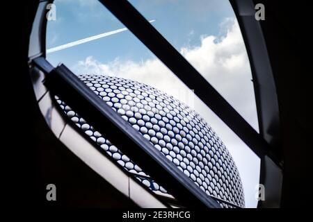 Birmingham UK Dicembre 2020 Centro commerciale Bullring guardando fino a. il cielo con le nuvole e l'aereo che sorvola l'architettura moderna con dischi in argento Foto Stock