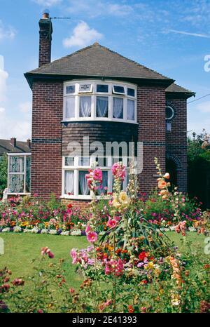 1920 / 30s casa indipendente di mattoni con giardino anteriore pieno di fiori evercreech somerset Foto Stock