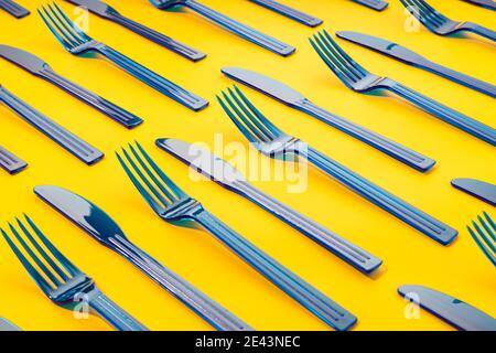 Vista dall'alto del telaio completo di forche e coltelli in plastica monouso disposti in ordine su sfondo giallo Foto Stock