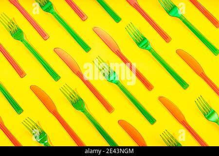 Vista dall'alto telaio completo di forche monouso colorate in plastica e. coltelli disposti in ordine su sfondo giallo Foto Stock