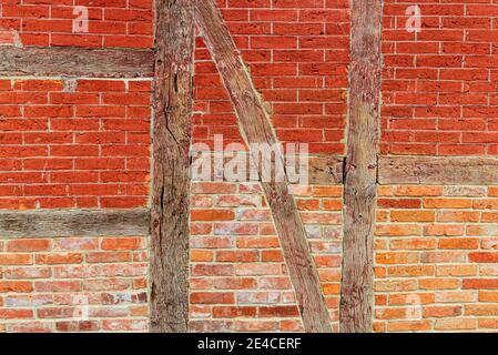Un muro di mattoni rossi in un rinforzo trasversale eseguito come una struttura a graticcio