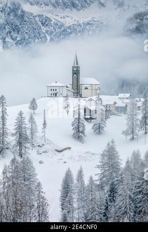Italia, Veneto, provincia di Belluno, Rocca Pietore, Agordino, il paese di Laste in inverno con la chiesa di San Gottardo sulla collina, Dolomiti Foto Stock
