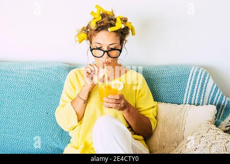 Colori gialli ritratto di bella giovane donna adulta caucasica che beve succo d'arancia sano a casa con arricciacapelli e divano blu in background - concetto di salute e stile di vita per le persone