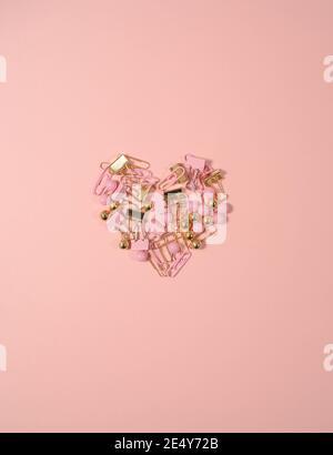 Sfondo creativo di San Valentino. Cuore realizzato con clip e spille di cancelleria colorate su sfondo rosa pastello. Sfondo del cuore. Concetto minimo, Foto Stock