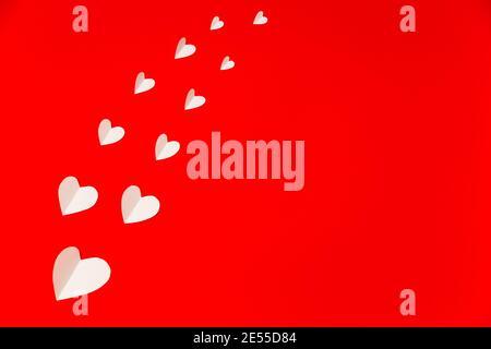 Cuori di carta bianca sullo sfondo rosso in stile piatto. Composizione per San Valentino. Concetto di vacanza Foto Stock