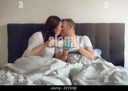 Felice coppia di mezza età baciandosi a letto nella tenuta del mattino una tazza di caffè Foto Stock