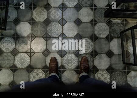Gamba uomo con stivali marroni grigio pavimento in pietra tessitura selettiva Focus sulle scarpe tonalità di colore vintage Foto Stock