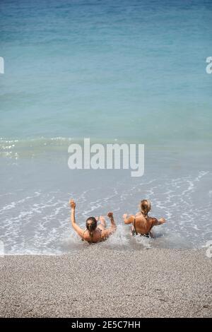 Due ragazze girlfriend sono seduti sulla spiaggia di sabbia del mare e le onde li hanno immersi in costumi da bagno su un giorno caldo e soleggiato