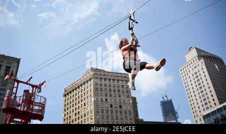 A woman rides a zip-line through the streets of Manhattan during New York City's 'Summer Streets' initiative in New York, August 11, 2012. The program, which is in its fifth year, invites the public to take part in various activities including bike riding, rock climbing and zip-lining, along closed streets throughout Manhattan from the Brooklyn Bridge to Central Park. REUTERS/Andrew Burton (UNITED STATES - Tags: SOCIETY)