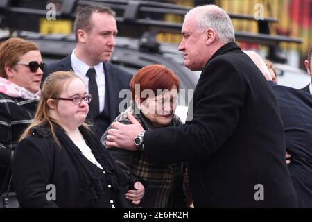 Sharon Ismad (C) è consolata da un lutto mentre lascia la chiesa dopo i funerali di suo marito, ufficiale di prigione Adrian Ismad alla Woodvale Methodist Church a Belfast, Irlanda del Nord 22 marzo 2016. IsmMay morì 11 giorni dopo l'esplosione di una bomba sotto il furgone che stava guidando. REUTERS/Clodagh Kilcoyne