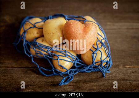Patate rosse a forma di cuore con patate bianche in una eco-griglia blu su uno sfondo di legno primo piano. Foto Stock