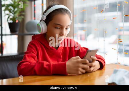Foto di una ragazza adolescente in una cuffia bianca durante le chat online con gli amici. Concetto di tecnologia moderna.