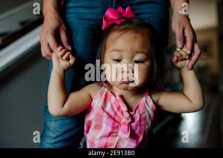 Pouting bambino asiatico con arco rosa in capelli imparare a. camminare