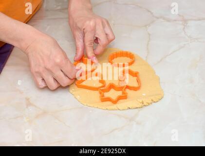 Donna che fa i biscotti usando la taglierina arancione di plastica Foto Stock