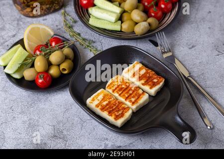 haloumi alla griglia su una padella nera con olive, pomodori, cetrioli e pepperoni. Primo piano.