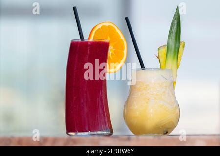 Cocktail preparati al momento con pezzi di frutta e paillette nere su un tavolo di legno. Messa a fuoco selettiva e primo piano. Concetto di svago e stile di vita.